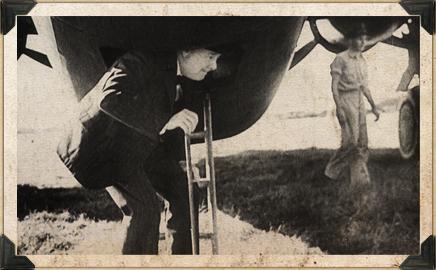 Winston Churchill crouching underneath a plane.
