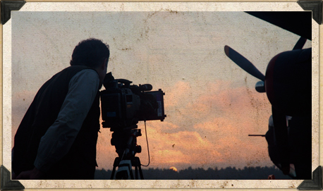 Bill standing behind a camera filming a plane in the distance at sunset.
